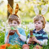 Two Little Boys Wearing Easter Bunny Ears And Eating Chocolate