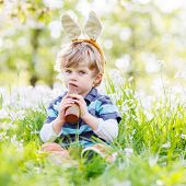 Funny Child Wearing Easter Bunny Ears And Eating Chocolate At Spring Green Grass