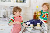 Two Little Lovely And Funny Kid Boys Washing Dishes In Domestic Kitchen