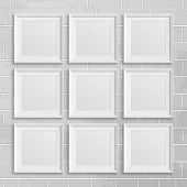 Set of square picture frames on brick wall