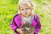 Little Girl Grimacing And Holding Nest With Eggs