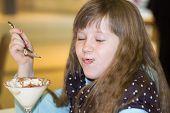 Little Girl Eating Ice Cream In Cafe
