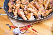 Roasted Chicken Drumsticks On A Frying Pan On The Cutting Board, With Garlic And Chilly Pepper And B