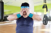 picture of obese man  - Fat man tired after workout and covering his face - JPG