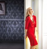 Mysterious blonde waiting next to white door