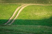 Rural Road Runs Through A Field Of Green Grass