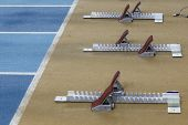 stock photo of start over  - Starting blocks in tart line over running track - JPG