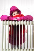 picture of freezing temperatures  - Freezing Young Girl in Winter Jacket Near a Heater - JPG