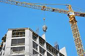 pic of mixer  - Crane lifting concrete mixer container against blue sky - JPG