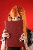 picture of peek  - Closeup of young redhead woman peeking over the edge of the closed book - JPG