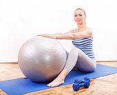 foto of pilates  - Young woman with Pilates ball sitting on blue mattress - JPG