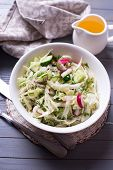 stock photo of grated radish  - Salad from cabbage herbs cucumber onion and radish in bowl on grey wooden background - JPG