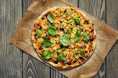 foto of italian parsley  - Delicious italian pizza on wooden background - JPG