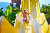 stock photo of excite  - excited man having fun on water slide in tropical aqua park - JPG