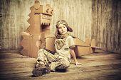 stock photo of dinosaur  - Cute dreamer boy playing with a cardboard airplane and dinosaur - JPG