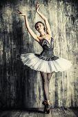 stock photo of ballet dancer  - Professional ballet dancer posing at studio over grunge background - JPG