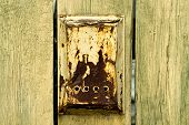 stock photo of mailbox  - Old rusty mailbox is hanging on old wooden fence with cracks - JPG