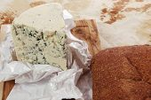 stock photo of deli  - aged italian deli fresh blue stilton cheese and rye ciabatta served on wooden cutting plate on used baking paper as background - JPG