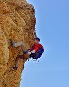 stock photo of climb up  - pioneer climbing up a yellow cliff - JPG