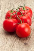 image of neat  - Bunch of neat red tomatoes on rustic wooden table - JPG