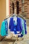 picture of thrift store  - New collection of clothes hanging on a rail outside - JPG