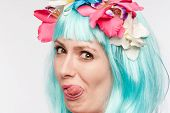 stock photo of headdress  - Girl with headdress and blue wig sticking her tongue out in studio on white background - JPG