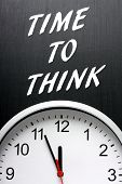 pic of midnight  - The phrase Time To Think in white text on a blackboard above a modern wall clock with the hands pointing towards midnight or twelve - JPG