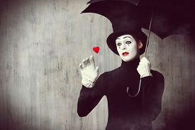 picture of pantomime  - Portrait of a male mime artist standing under umbrella expressing sadness and loneliness - JPG