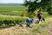 Casal sentado-se na grama na frente de vinhas