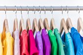 Fashion clothes on clothing rack - bright colorful closet. Closeup of rainbow color choice of trendy poster