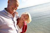 Paar lächelnd Senioren haben einen Spaziergang am Rande des Meeres