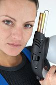 Portrait of a young woman holding a blowtorch
