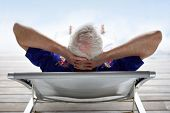 stock photo of 55-60 years old  - Senior man relaxing in a deck chair - JPG