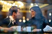 stock photo of voyeur  - Happy young couple in cafe having a great time together. View through cafe window.