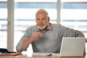 stock photo of senior men  - Portrait of a senior man sitting at a desk in front of a laptop computer - JPG