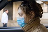 Young woman travels on automobile in a protective mask