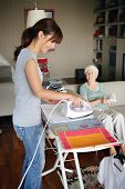 Young woman ironing near a senior woman sitting on a sofa with a book