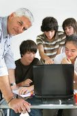 Portrait of a man and a group of teenagers in front of a laptop computer in a classroom