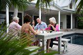 Senior group having a dinner on a terrace near a swimming pool