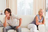 Triste casal sentado em um sofá