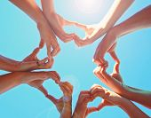 overhead view of a group of people making heart shapes with their hands directly below the sun with  poster