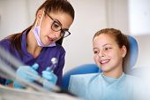 Female dentist showing instrument for repairing teeth to girl in dental chair poster