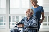 Tranquil Senior Husband Sitting In Wheelchair And Holding The Bible. His Calm Wife Standing Near Him poster
