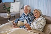 Tranquil Elderly Couple Surfing The Internet In Bedroom. They Are Looking At Devices And Reading New poster