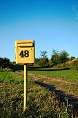 Closeup Of A Square Yellow Mailbox Number 48 poster