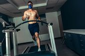 Runner With Mask Doing A Performance Test On Treadmill poster