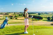 Side view of a fit woman wearing modern golf outfits, while looking at the horizon on the green gras poster