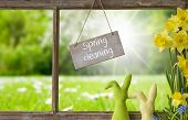Sign With English Text Spring Cleaning. Window Frame With View To Beautiful Sunny Green Meadow. East poster