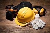 Close-up Of Yellow Hard Hat With Safety Equipment On Wooden Background poster