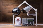 Cctv Camera And Security Alarm System Under The House Made With Measuring Tape poster